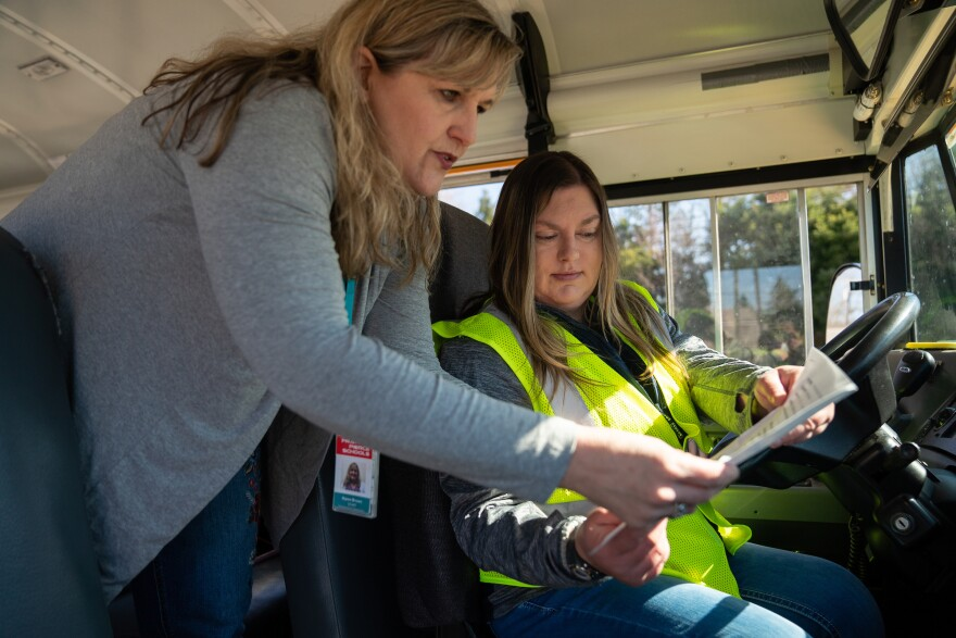 Franklin Pierce Schools bus driver Karrie Nilles (right), and nutrition services director Karen Brown look over a list of the district's meal distribution sites.