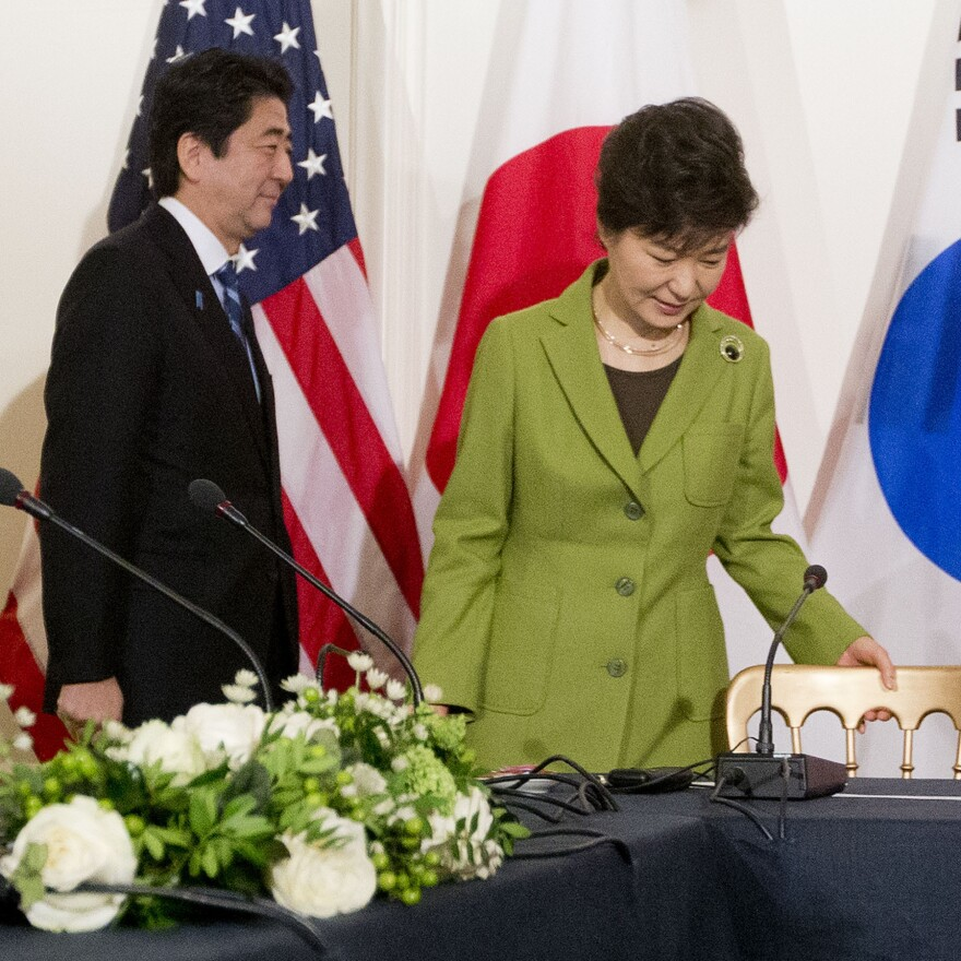 Japanese Prime Minister Shinzo Abe and South Korean President Park Geun-hye walk to their seats for the start of a trilateral meeting with the U.S. in 2014. Japan and Korea's leaders have yet to meet one-on-one.