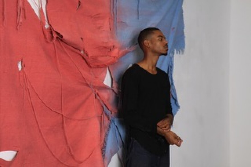 Vaughn Davis stands in front of one of his works, a red and blue shredded canvas.