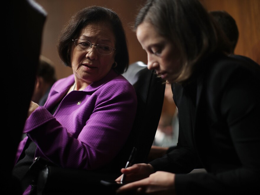 Hirono talks to an aide during the confirmation hearing of FBI Director nominee Christopher Wray.