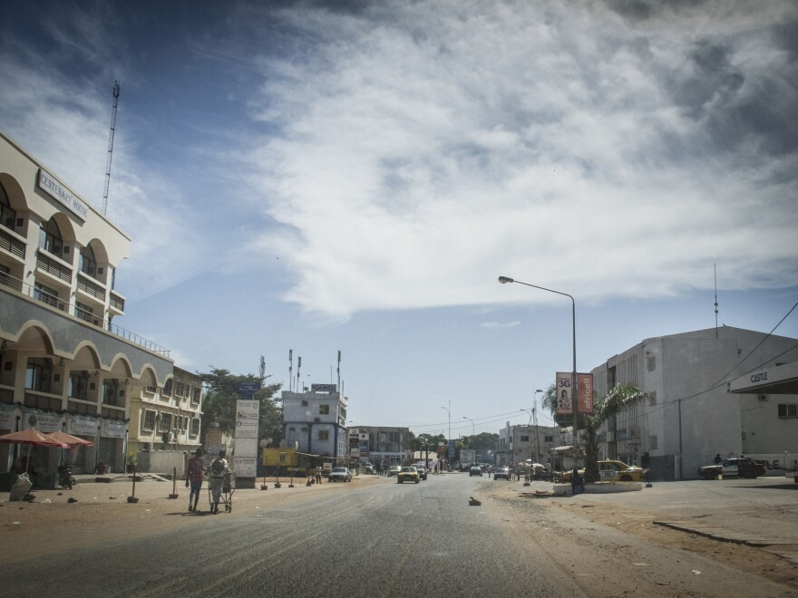 Residents walk on an empty street in Banjul Gambia, Tuesday, Dec. 30. Heavy gunfire rang out Tuesday near the presidential palace, raising the specter of a coup attempt.