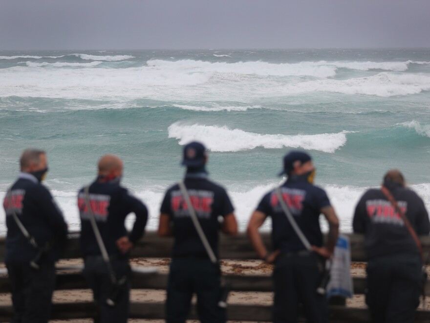Palm Beach County Fire Rescue check out the ocean as waves crash ashore from Tropical Storm Isaias as it passes through the area on August 2, 2020 in Juno Beach, Fla.