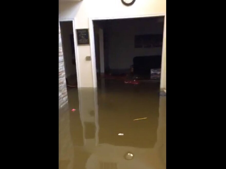 """A screenshot from Mayor Derrick Harvey's Facebook livestream on Wednesday. """"We got some water, y'all. Harvey wasn't playing,"""" the Mayor says in a video that shows knee-deep water inside his house."""