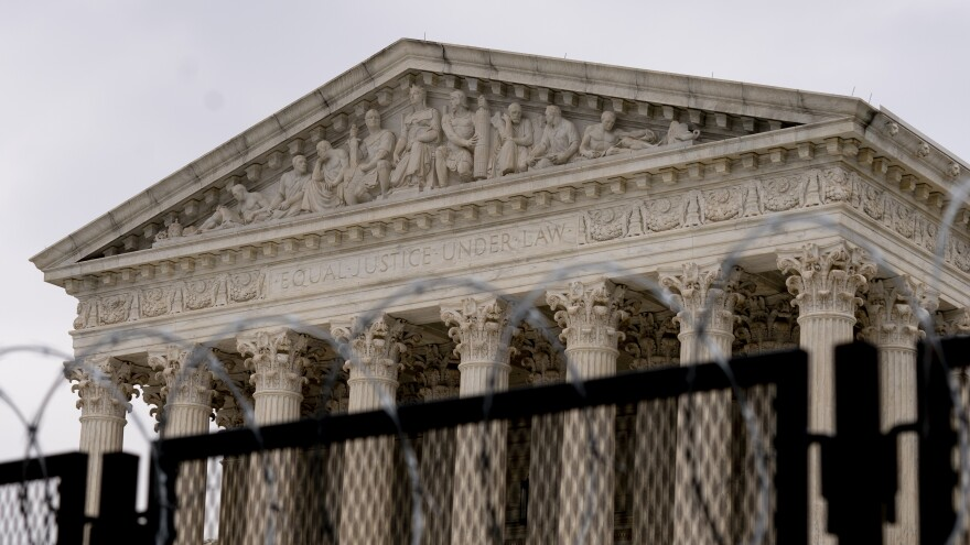 The U.S. Supreme Court, surrounded by a security fence on Feb. 10, said Monday it would take up a challenge to Trump-era abortion rules.