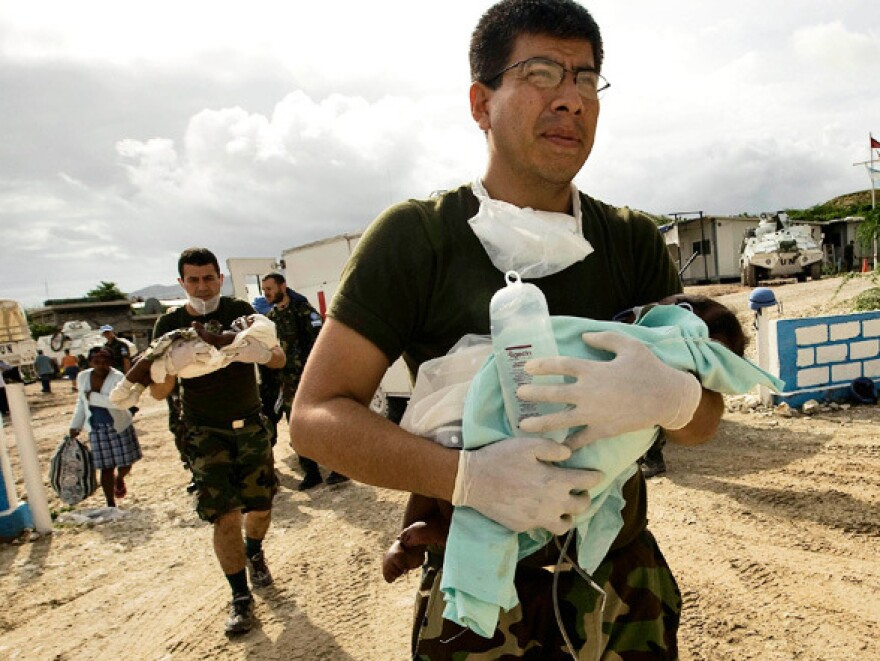 In Haiti, an Argentinean U.N. doctor carries a sick baby to a helicopter, to be taken to Port-au-Prince for treatment. The photo is part of a gallery honoring World Humanitarian Day.