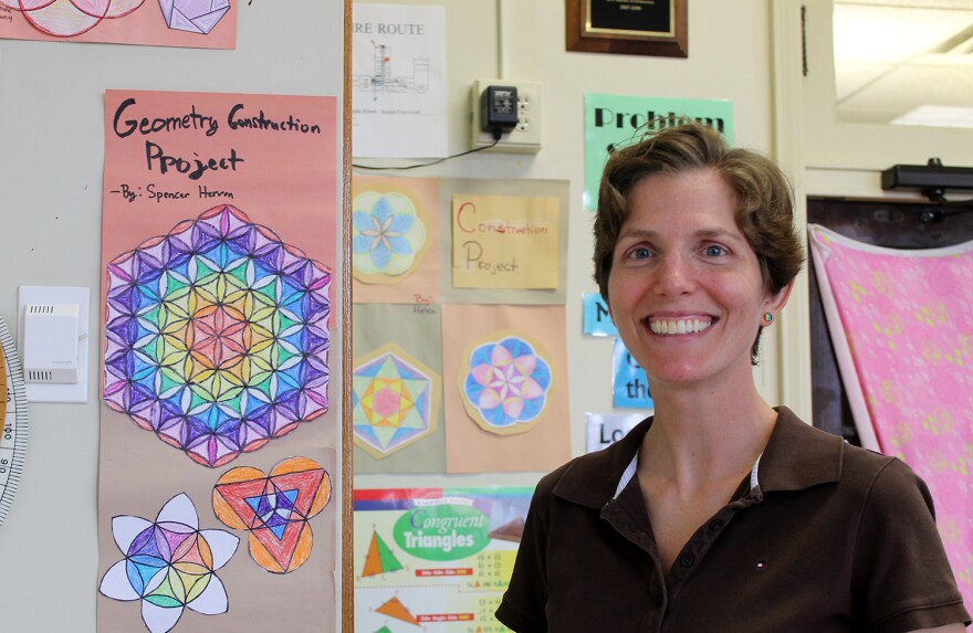 Middle school math teacher Krystal White poses in front of old geometry projects in her classroom at MICDS on Aug. 10, 2016.