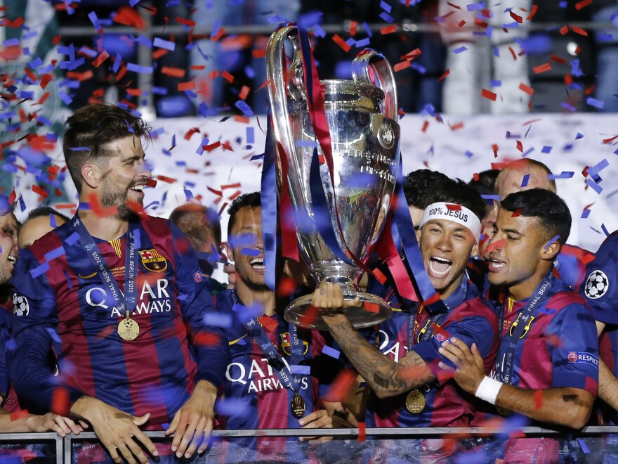 Barcelona's Gerard Pique (left) and Neymar (wearing headband) celebrate with the trophy after the Champions League final soccer match between Juventus Turin and FC Barcelona in June.