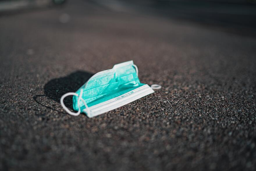 a teal medical mask has been discarded on the road