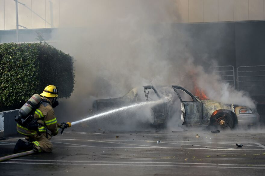 A firefighter extinguishes flames from a burning car following a demonstration in Santa Monica, Calif., on Sunday.