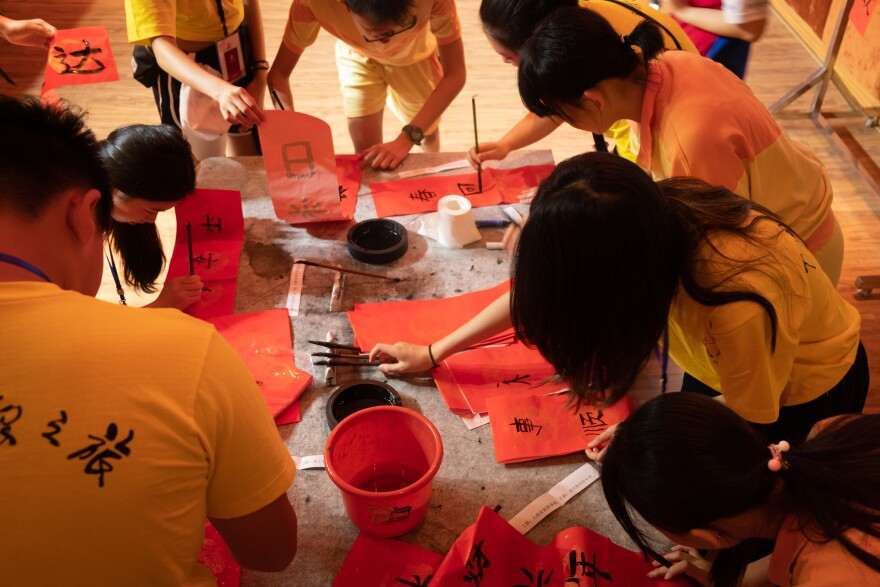 Local students as well as ethnic Chinese students from abroad attend a Chinese calligraphy class.