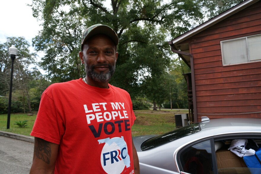 """James Allen Ollins smiles at the camera. He wears a red shirt that reads, """"Let My People Vote. FRRC."""" Behind him is a rural neighborhood."""