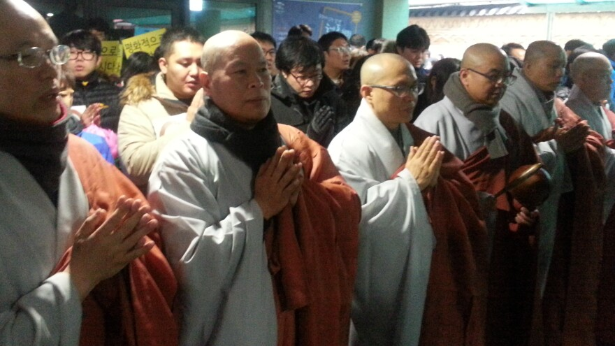 Monks chanting outside the entrance to a building at Seoul's Jogye Temple, as police prepared to raid it to arrest a labor leader seeking refuge inside. The raid was postponed Wednesday.