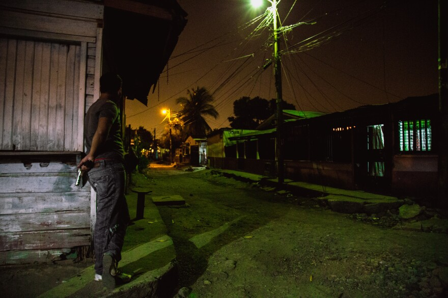 A gang member protects a block of their turf in San Pedro Sula. The decades-long fighting has made enemies of people who might live just a block away from each other, says Ayuso.