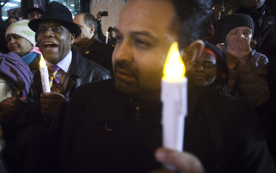 People sing as they take part in a prayer vigil at the site where two police officers were shot to death in the Brooklyn borough of New York this weekend.