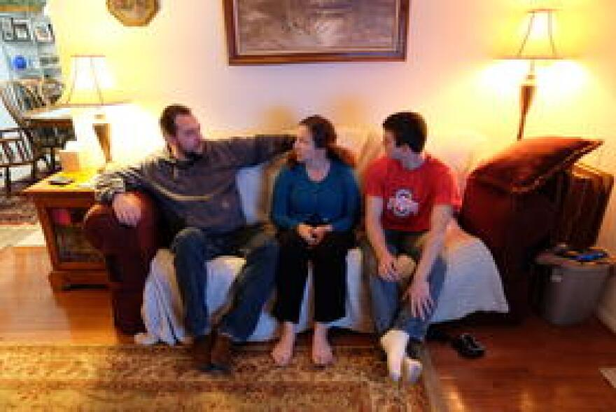 Kent, Brenda, and Alex Davis chat and laugh together on the couch after dinner.
