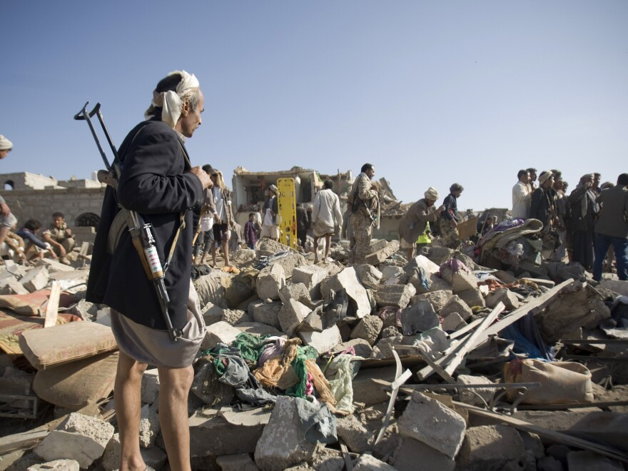 A Houthi Shiite fighter stands guard Thursday as people search for survivors under the rubble of houses destroyed by Saudi airstrikes near Sanaa Airport in Yemen.