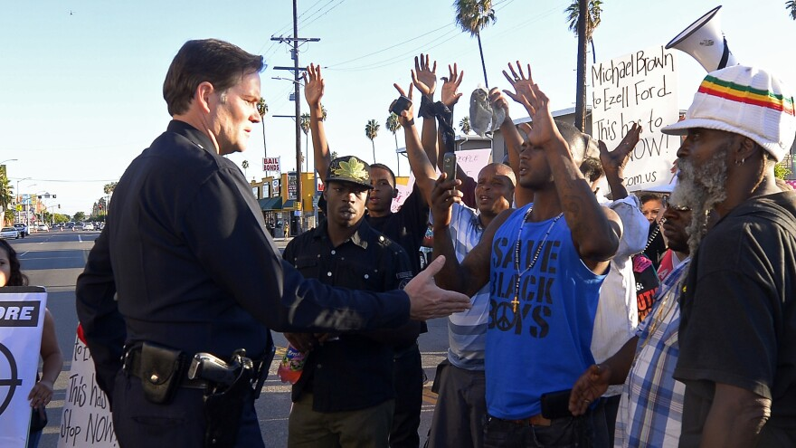 Protesters hold their hands up as an LAPD officer talks on Aug. 14 in the aftermath of the shooting of a 25-year-old African-American man. The department says confidence in the LAPD has helped head off the kind of unrest seen in Ferguson, Mo., over the shooting of 18-year-old Michael Brown.
