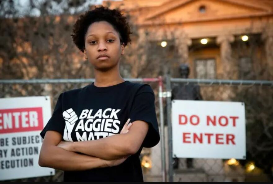 """Qynetta Caston, a student at Texas A&M, stands in front of the statue of former Texas A&M President Lawrence Sullivan """"Sul"""" Ross."""