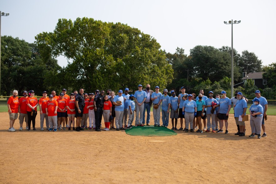 People pose on the field for a group photo with each team wearing their respective orange and blue uniforms.  The Arlington mayor, the new chief of police in Arlington and the member of the city council are putting the teams ahead of the classic league in Saturday's matches.