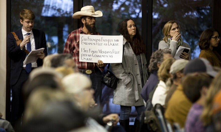 "A man carries a sign in protest of the planned pipeline at the Wimberley Community Center Tuesday night. His sign says, sign says, ""Our Founding Fathers saw England's rule as unjust. I see Kinder Morgan's rule over my community as unjust."""