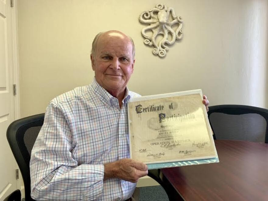 Tom Botchie with his scrapbook of memories from his time in the Air Force. On the front cover is the participation certificate he received decades ago after completing his service in Operation Hardtack. Now atomic veterans are getting a new certificate to