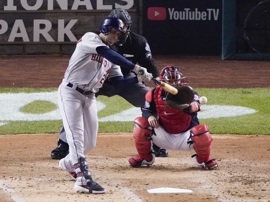 Houston Astros' Michael Brantley hits an RBI single during the third inning of Game 3 of the baseball World Series against the Washington Nationals in Washington.