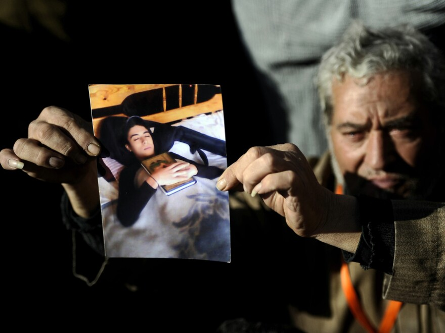 A protester shows a picture of his son, who was killed at a rally in Cairo's Tahrir Square on Dec. 23. Soldiers at the rally were taped beating female protesters, sparking international outrage. Advocates say there has not been similar anger over the deaths of children.