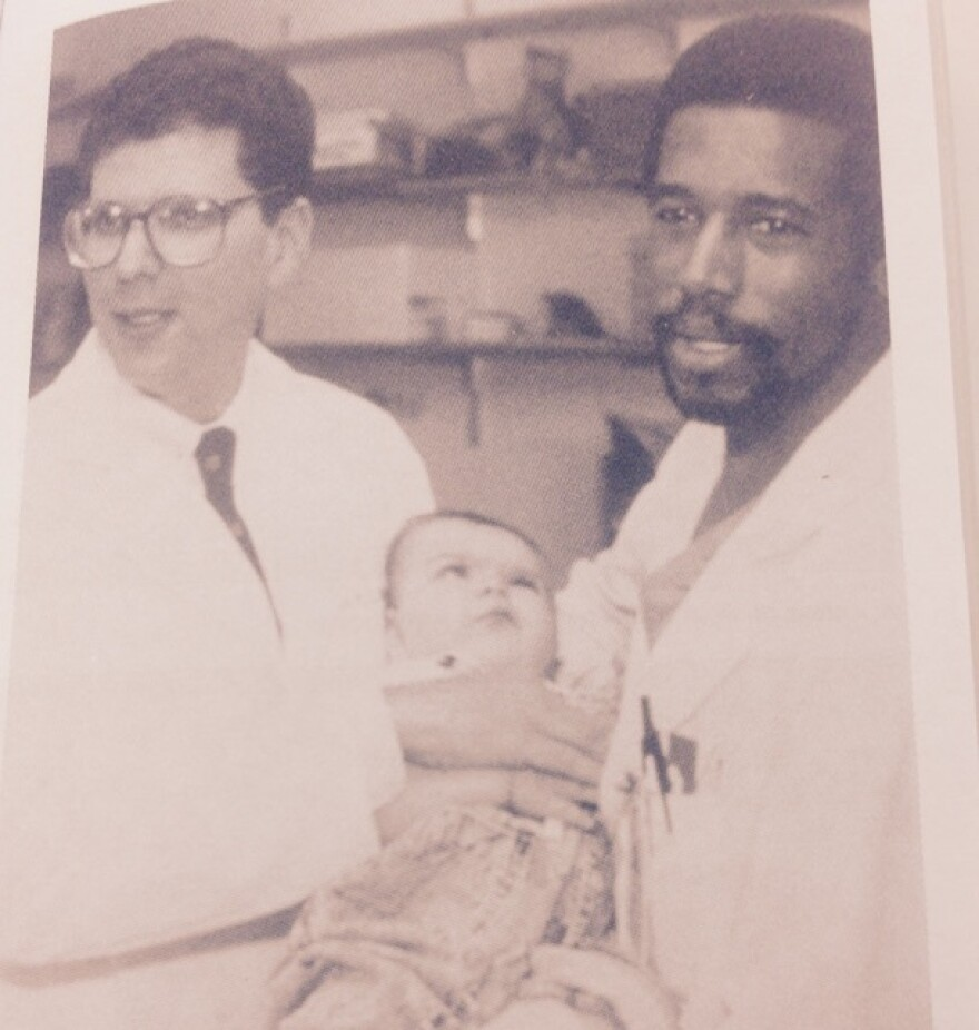Dr. Ben Carson (right) poses with Dr. Mark Rogers and one of the Binder twins whom Carson surgically separated in a first-of-its kind operation. The twins were born conjoined at the head.