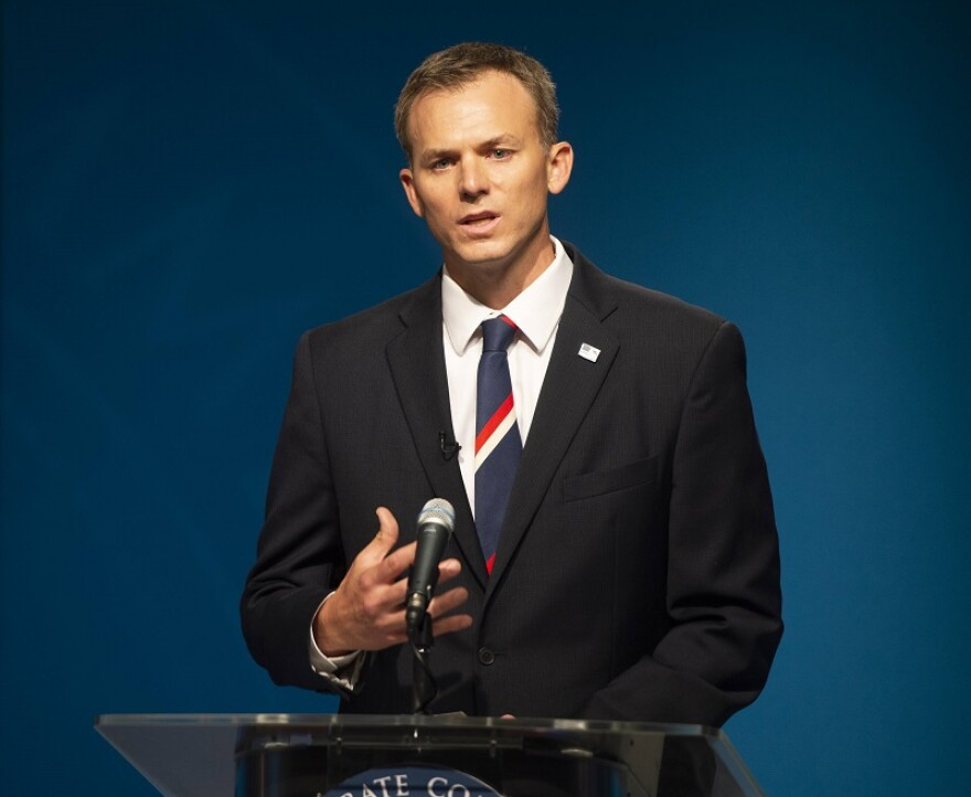 Photo of a man in a suit and tie standing at a podium.