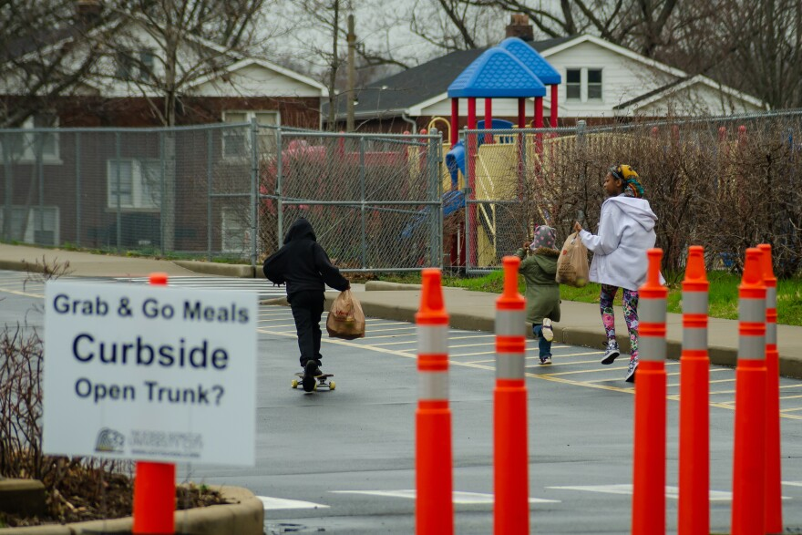 Children leave Pershing Elementary School on March 26, 2020, after picking up lunch. Some districts in the state have cut back student meal services after employees got sick.