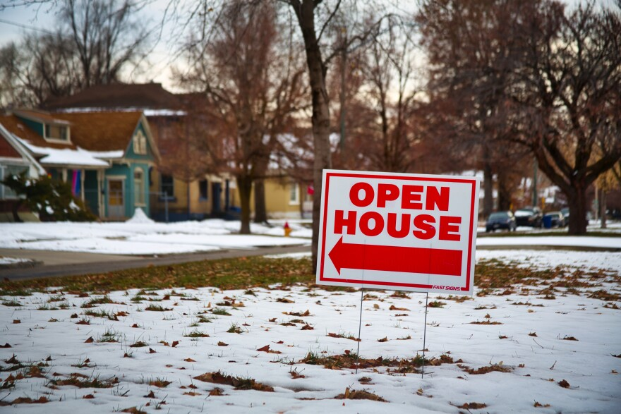 """Photo of a sign that reads """"open house"""" on a front lawn."""