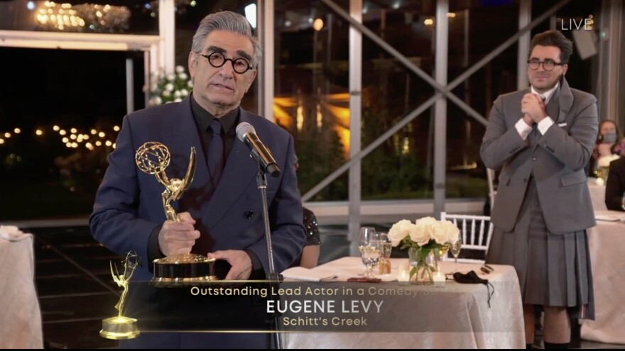 Eugene Levy accepts his award for lead actor in a comedy series for <em>Schitt's Creek </em>as his son (and creative partner) Dan Levy looks on at Sunday night's Emmy Awards.