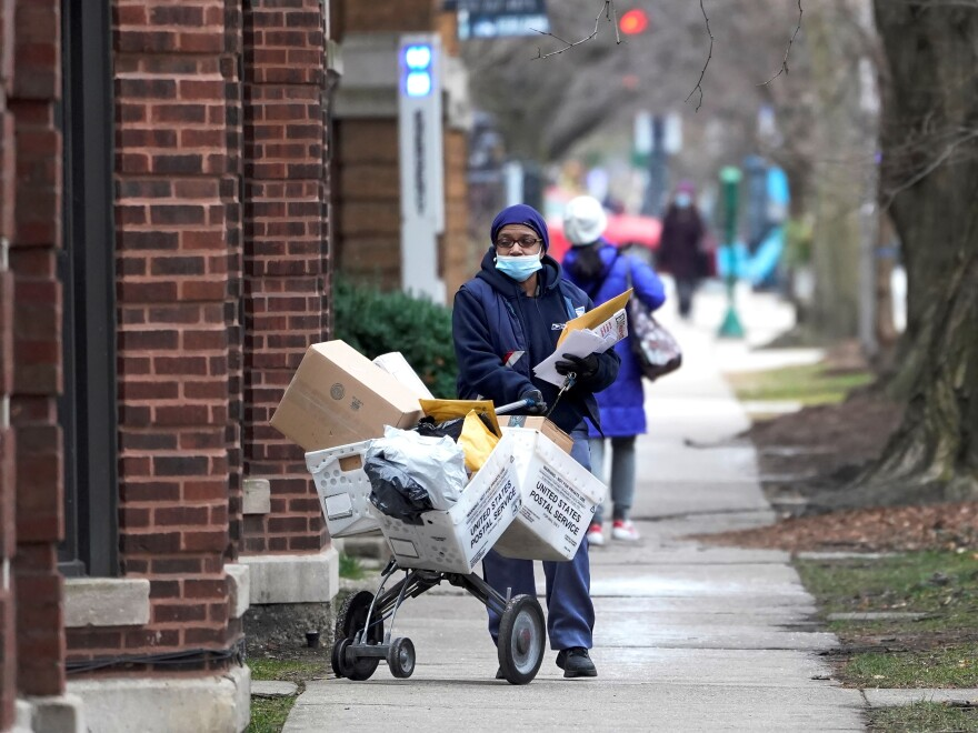 "A U.S. postal worker delivers packages, boxes and letters Tuesday, Dec. 22, 2020, along her route in the Hyde Park neighborhood of Chicago, just three days before Christmas. The U.S. Postal Service said it faces ""unprecedented volume increases and limited employee availability due to the impacts of COVID-19."""