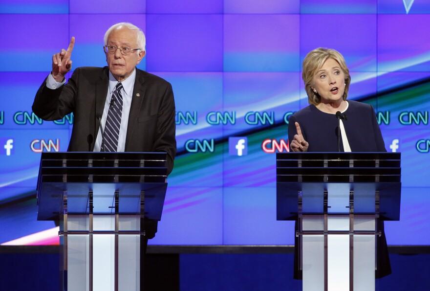 Hillary Clinton and Sen. Bernie Sanders of Vermont speak during the CNN Democratic presidential debate on Tuesday.