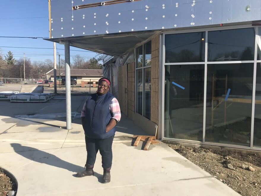 General Manager Leah Bahan-Harris stands outside the Gem City Market while it is in its final stages of construction. The building has exposed metal and plywood panels along an entrance.  Bahan-Harris is smiling, wearing a navy blue winter vest, a pink plaid shirt and work boots.