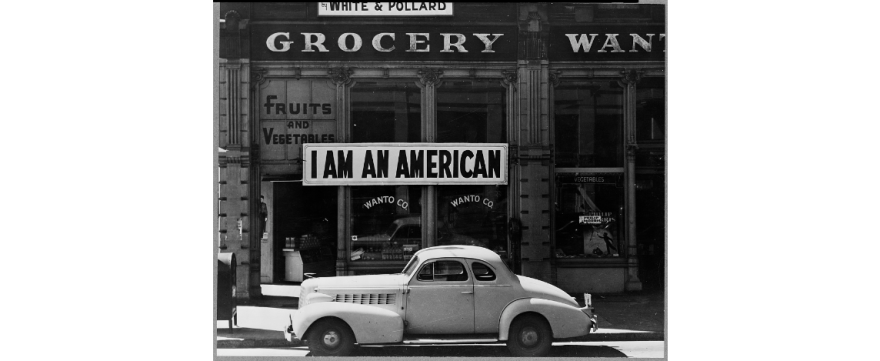 "A picture of a large sign reads ""I am an American"" hangs in a window of a store in Oakland, CA."