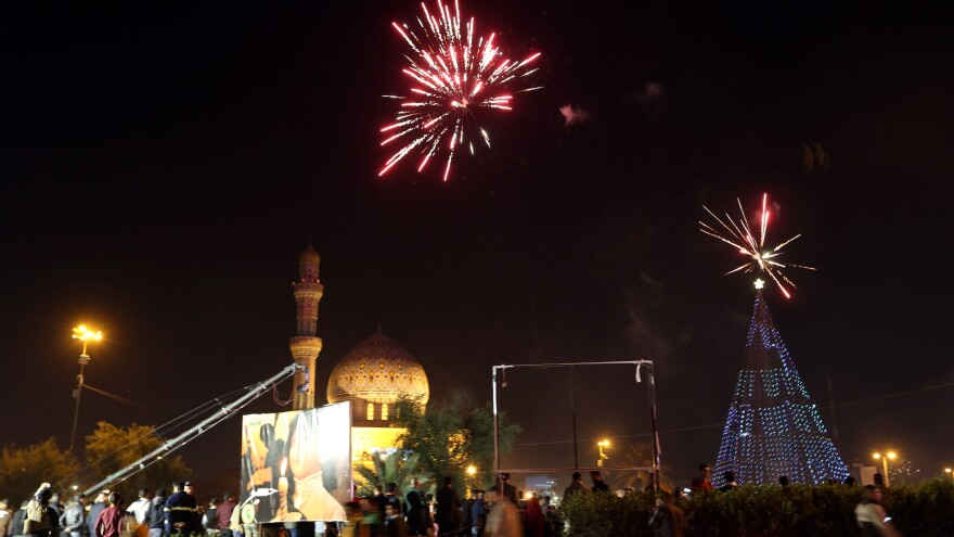 Iraqi crowds cheer as the countdown and fireworks begin during a New Year's Day celebration at Firdos Square in Baghdad on Wednesday.