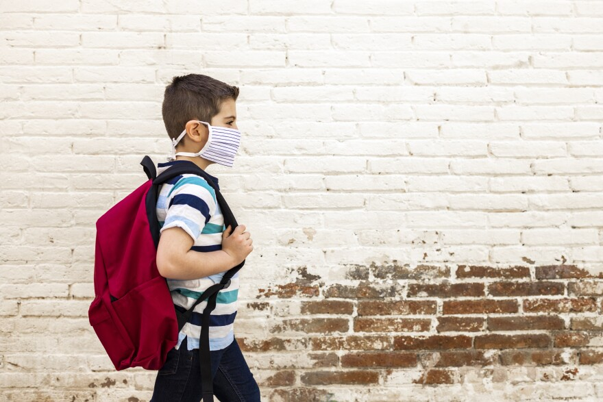 boy wearing a mask and carrying a backpack walks in front of a wall