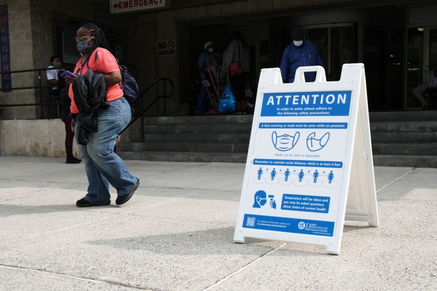 A sign in front of a hospital instructs people to wear face masks in the Brooklyn borough of New York City.