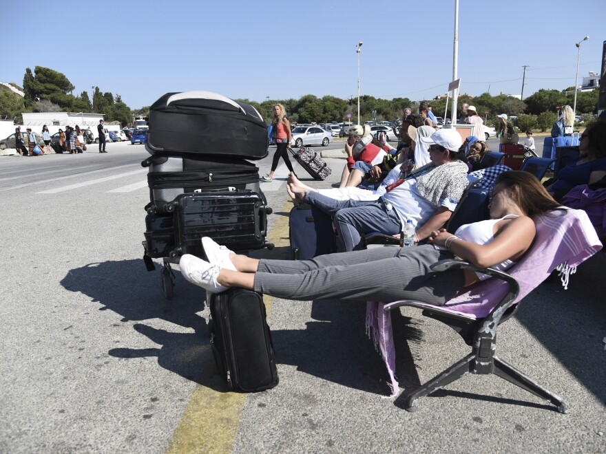 Travelers gather outside the airport on the Greek island of Kos. Many flights were canceled in the aftermath of a magnitude 6.7 earthquake.