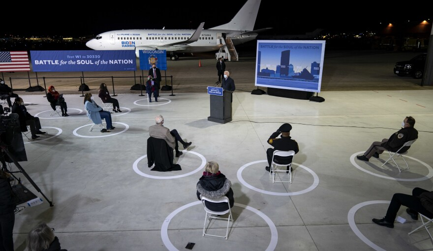 With a socially distanced audience of supporters and journalists, Democratic presidential nominee Joe Biden delivers remarks at Milwaukee Mitchell International Airport in Wisconsin on Friday.