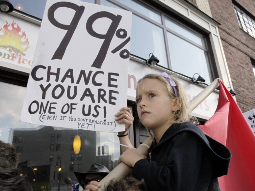 <p>Luoisiana Harris, 7, marches with Occupy Wall Street protesters from their base in Zuccotti Park toward Washington Square last Saturday. Harvard professor Lawrence Lessig says the Occupy Wall Street movement and the Tea Party share some similar concerns.</p>