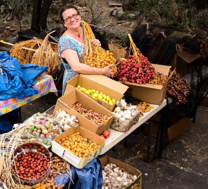 Barbara Eiswerth, founder and director of Iskashitaa, sorts fresh dates gathered by refugees and volunteers in neighborhoods around Tucson, Ariz.