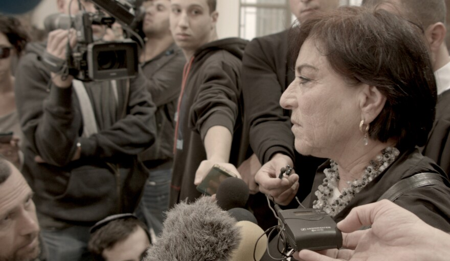Israeli lawyer Lea Tsemel is shown in <em>Advocate</em> speaking to a scrum of reporters at a Jerusalem courthouse.