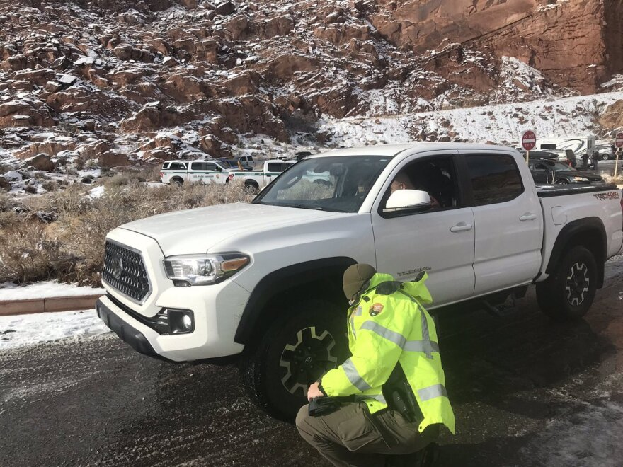 A photo of a man inspecting a tire of a white truck.