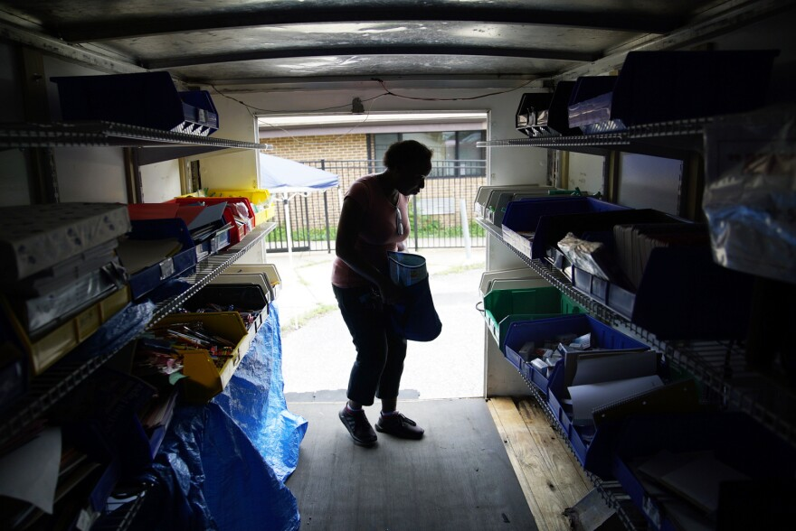 A Dayspring Head Start employee chooses school supplies in the back of the Supply Mobile box truck.