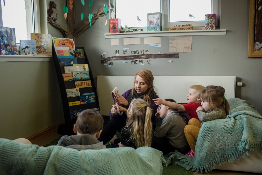 "Colleen Macleod reads to children at Pairc Playgroup in South Lochs. The childcare center offers bilingual learning and says the mobile library is critical for access to Gaelic children's books. ""As educators, we use it for resources and that keeps the culture alive as well,"" says teacher Kayleigh Makillop."