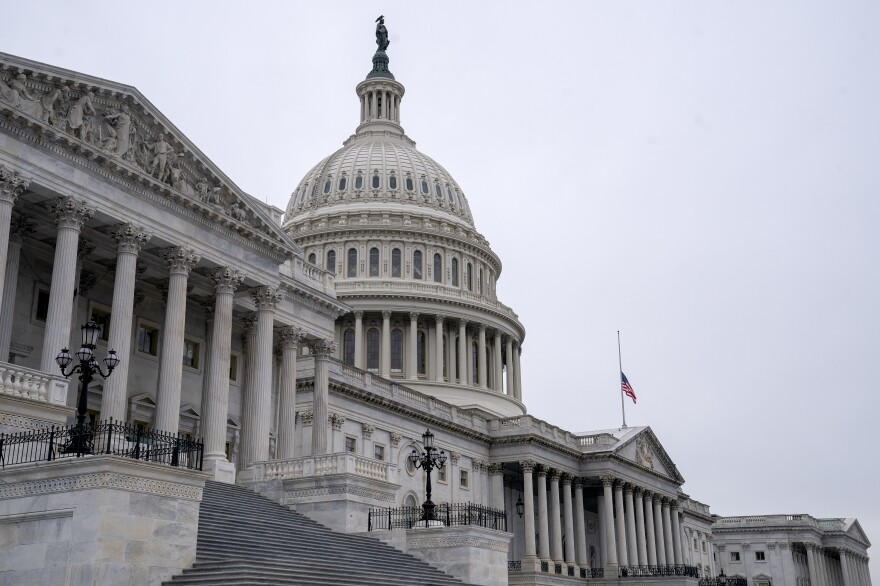 An American flag flies at half staff at the U.S. Capitol on Monday to honor two U.S. Capitol Police officers who died following the violence on Capitol Hill.