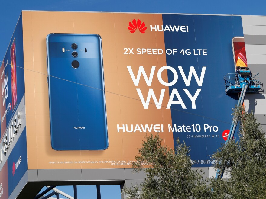 A crew hangs a Huawei advertising banner on the side of the Las Vegas Convention Center in January. Some senators want to ban it the world's third-largest seller of smartphones from the U.S.