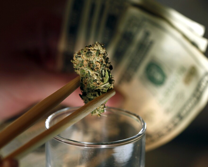 "A marijuana bud and cash at a shop in Denver. An owner of marijuana stores in the city says of his company's bank account, ""We treat it like gold."""